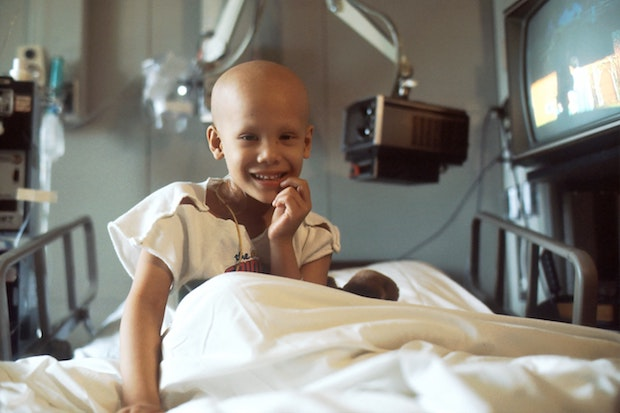 A young girl receiving chemotherapy in her hospital bed